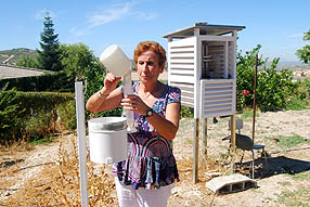 Victoria Marín comprueba que el pluviómetro sigue vacío antes  de dar por acabado el  año agrícola