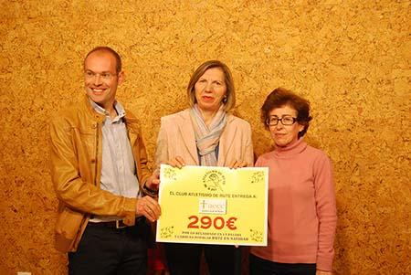 Juana Serrano, presidenta de la Junta Local,  recibe de Juan Manuel Aguilar el cheque simbólico del Club Atletismo Rute