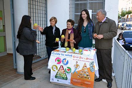 Profesionales sanitarios y voluntarios han  repartido folletos informativos y manzanas como ejemplo de alimentación  saludable