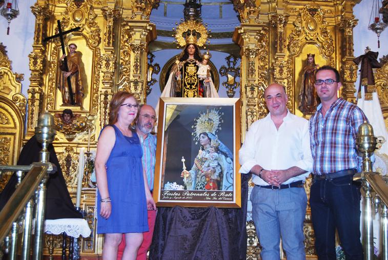 El alcalde y José Macías, como autor de la instantánea, muestran junto a los hermanos mayores el cartel de estas fiestas