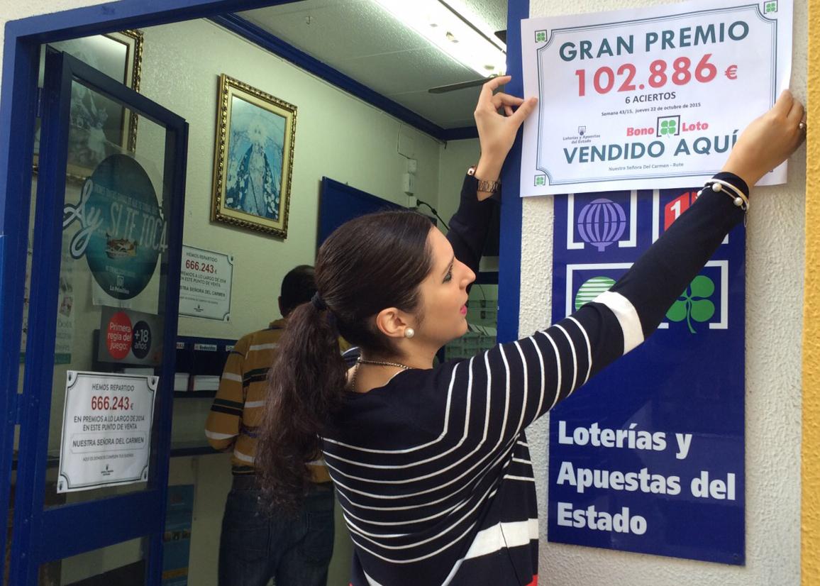 Loli Rabasco pega en la puerta de la administración el cartel que acredita que han repartido la suerte