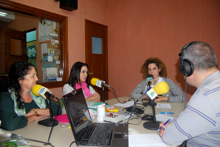 Las tres mujeres promotoras de la actividad muestran en Radio Rute los gorritos que se hacen para los niños