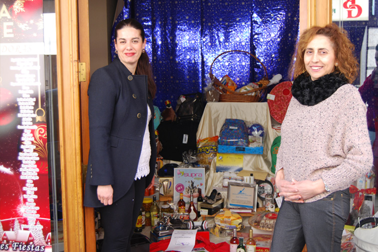 Paqui Rabasco, a la derecha, abre las puertas del local a Mariceli Aroca para que vaya retirando los regalos de la cesta